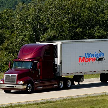 Truck on freeway with weigh-more weighbridge seller branding